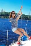 Navigação da mulher em um iate em óculos de sol elegantes imagens de stock