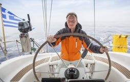Navigação do homem novo no mar Capitão do iate sailing fotografia de stock