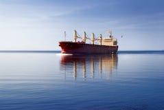 Navigação do navio de carga na água imóvel Fotografia de Stock Royalty Free