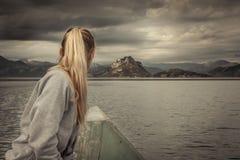 A navigação do viajante da mulher no barco para a costa com com as montanhas ajardina no horizonte no dia nublado com céu dramáti Foto de Stock