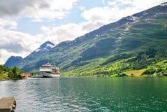 Navigação luxuosa do navio de cruzeiros das montanhas de Noruega do porto no fundo Foto de Stock