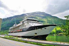 Navigação luxuosa do navio de cruzeiros das montanhas de Noruega do porto no fundo Fotos de Stock Royalty Free