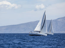 Navigação no vento através das ondas no Mar Egeu em Grécia Fileiras de iate luxuosos na doca do porto imagem de stock royalty free