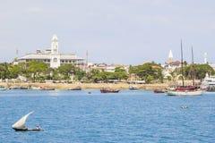 Navigação pequena da embarcação na frente da cidade de pedra imagem de stock royalty free