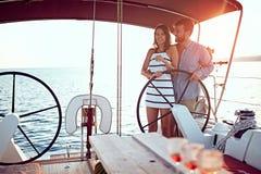 Navigação romântica do homem e da mulher no barco luxuoso junto e para apreciar no por do sol imagens de stock
