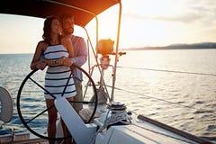 Navigação romântica dos pares no barco luxuoso junto e para apreciar no por do sol fotografia de stock royalty free