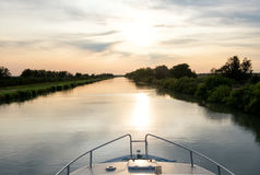 Navigando al tramonto su un canale navigabile nel Camargue Fotografia Stock