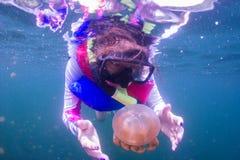 Navigando usando una presa d'aria nel lago jellyfish con il giubbotto di salvataggio immagini stock