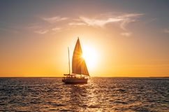 Navigando yacht nell'oceano al tramonto immagine stock libera da diritti