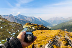 Navigate with GPS in the mountain. GPS navigator and hand on Alps mountain background Royalty Free Stock Images
