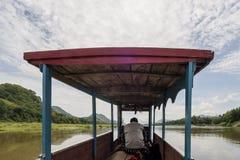 Navigatie op de Mekong Rivier in Luang Prabang, Laos, met een typische houten boot stock foto's