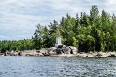 Navigatieteken op de rotsen op de kust van het meer van Ladoga Stock Foto
