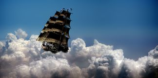 Navigating on Clouds. Sailboat navigating on white cumulonimbus clouds under a crystal clear blue sky Stock Photos