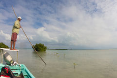 Navigating on the flats of Belize with flyfishing boat. The guide is using a push pole to approach the fish silently. Targeted species are Bonefish and Permits royalty free stock image