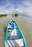 Navigating on the flats of Belize with flyfishing boat. The guide is using a push pole to approach the fish silently Royalty Free Stock Photography