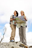 Navigating map women. Two cheerful women hiking outdoors and consulting their map for the direction in which to travel stock photos
