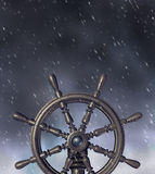 Navigating Through the Storm. Navigating a through a storm and dangerous challenges with wind and rain as a ship wheel icon as a business leadership symbol and Stock Photos