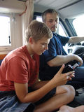 Navigation. The teenager with the gps-navigator, prompts a route to the driver of the automobile stock image