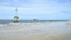Navigation beacon with freight ship in background Royalty Free Stock Photography