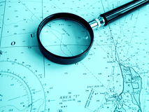 Navigation chart with magnifier. An image showing a sea navigating chart or map, taken with a magnifying glass placed on top.  Suggests planning of an Royalty Free Stock Image