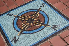 Navigation compass mosaic on the ground stock photos