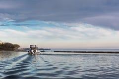 Navigation de bateau sur un paysage de lac avec les cieux nuageux images stock