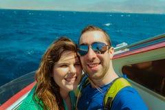 Navigation heureuse de couples sur un bateau et selfie de prise avec le smartphone Photos stock