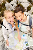 Navigation outdoor. Two cheerful women hiking outdoors and consulting their map for the direction in which to travel stock images