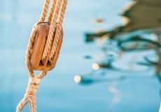 Navigation, poulie en bois avec les cordes nautiques et eau de mer bleue image libre de droits