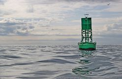 Navigational buoy in calm seas with clouds Stock Photo