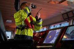 Free Navigator. Pilot, Captain As Part Of Ship Crew Performing Daily Duties With VHF Radio, Binoculars On Board Of Modern Ship With Stock Image - 155250561
