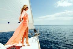 Navigazione da diporto di lusso di pareo della donna in mare con luce solare del cielo blu Immagini Stock