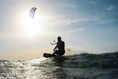 Navigazione del surfista dell'aquilone davanti al tramonto Fotografia Stock