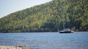 Navigazione dell'vuoto-albero della barca contro la corrente di un fiume su fondo della foresta mista del pendio in un giorno sol video d archivio