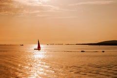 Navigazione dell'yacht al tramonto nel mare Fotografie Stock