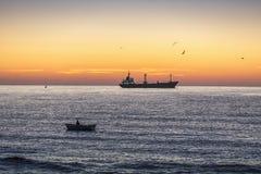 Navigazione della nave da carico e del pescatore nel mare su alba Fotografie Stock Libere da Diritti