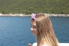 Navigazione felice della bambina in una barca che sorride al mare su crociera di estate immagini stock