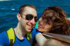Navigazione felice delle coppie su una barca e selfie di presa con lo smartphone Fotografia Stock
