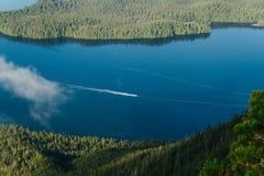 Navigazione sola della barca sull'acqua blu fra due isole con la foresta Fotografie Stock Libere da Diritti