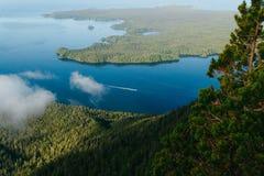 Navigazione sola della barca sull'acqua blu fra due isole con la foresta Fotografia Stock Libera da Diritti
