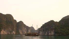 Navigazione tradizionale della barca di crociera del ciarpame nella baia di lunghezza dell'ha, Vietnam stock footage