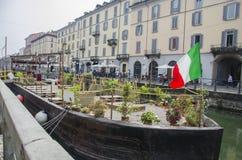 Naviglio重创的运河在米兰,意大利 站立在Naviglio运河和等待的a的水的小船restouran 库存照片