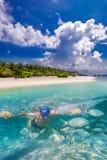 Naviguant au schnorchel sur l'île tropicale avec des pavillons de plage sablonneuse et d'overwater, les Maldives Photographie stock libre de droits