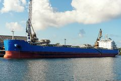Navio de carga azul grande do bulker amarrado no porto da carga durante a opera??o da carga fotografia de stock royalty free