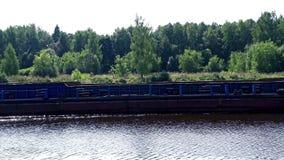 Navio de carga vazio que flutua ao longo do rio no barco de carga da floresta do fundo filme