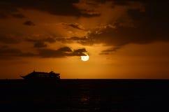 Navio de cruzeiros mostrado em silhueta contra o céu do por do sol Imagens de Stock