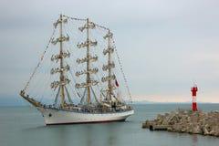 Navio de navigação velho na frente do farol Foto de Stock