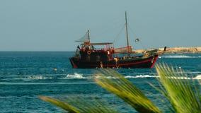 navio de navigação velho Vista através das partes superiores das palmeiras Fotos de Stock