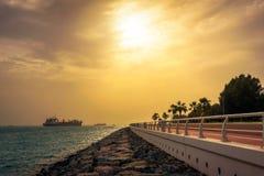 Navio de recipiente da carga que sae do porto de Dubai no por do sol Fotos de Stock Royalty Free