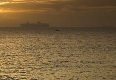 Navio de recipiente mostrado em silhueta contra o horizonte no nascer do sol Foto de Stock Royalty Free